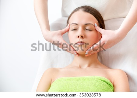 masseur makes massage of the face of brunette in a towel  - stock photo