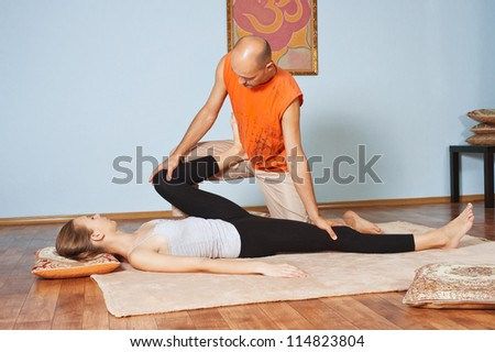 Masseur makes Thai massage girl - stock photo