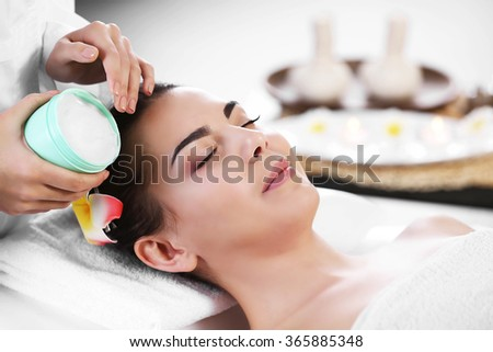 Masseur putting cream on woman's face during massage process at beauty spa - stock photo