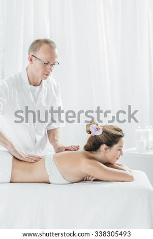 Masseur therapist and female customer in spa