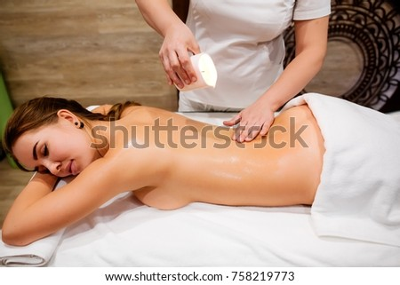 Masseur woman drips wax from a candle on the back of a young girl, preparing for the massage