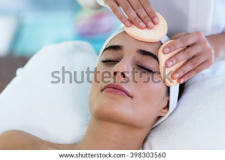 Masseuse cleaning woman face with cotton swabs at spa - stock photo