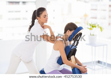 Masseuse giving back massage to woman on chair at spa - stock photo