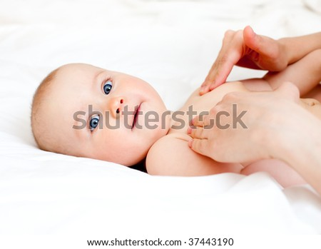 Masseuse massaging little baby girl, shallow focus