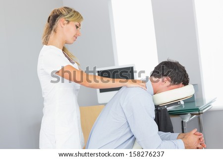 Masseuse treating shoulders of client in massage chair in bright room