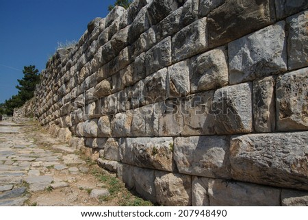 Massive ashlar masonry wall along a street near the agora of the ancient city of  Priene,  Turkey - stock photo