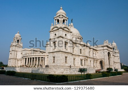 Massive building of Victoria Memorial Hall of Kolkata at the sunny day. The memorial was designed by Sir William Emerson using Indo-Saracenic style, incorporating Mughal elements in the structure. - stock photo