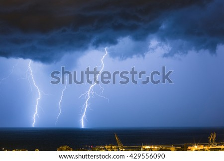 Massive cloud to ground lightning bolts hitting the horizon of city lights - stock photo
