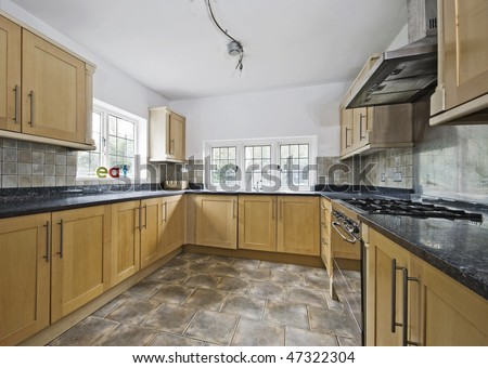 massive cottage style kitchen in wooden finish and granite worktop - stock photo