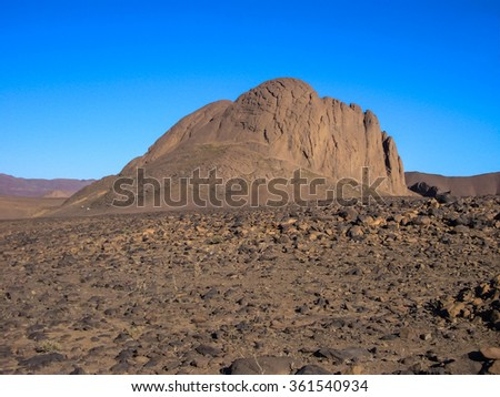 Massive geological rock in the middle of Hoggar desert in Algeria - stock photo