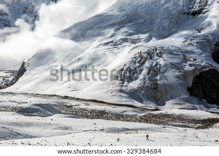 Massive Glacier at High Altitude Severe Mountains and Small Body of Alpine Climber with Backpack and Trekking Poles Walking on Ice Surface with Clouds Moving Down and Sun Beams