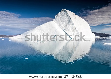 Massive iceberg floating near Eqi Glacier in Greenland. An iceberg is a large piece of freshwater ice that has broken off a glacier or an ice shelf and is floating freely in open water. - stock photo