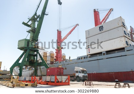 Massive port crane is lifting a container from cargo truck in order to load a container ship at container terminal at Varna port, Varna, Bulgaria, May 16, 2014.