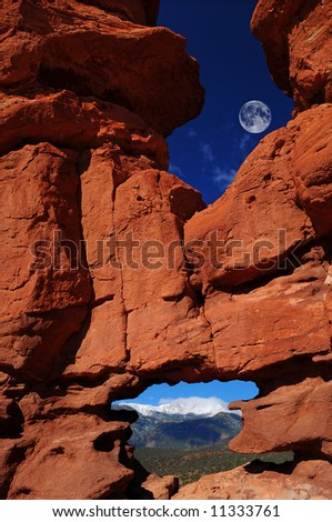 "Massive rock formations nick-named ""Siamese Twins"" at the Garden of the Gods Park in Colorado Springs, Colorado with Pikes Peak showing through the bottom window - stock photo"
