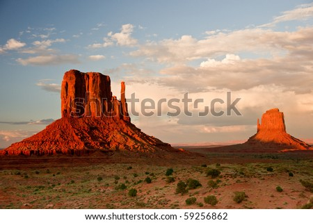 Massive sandstone pillars soar above iconic Monument Valley at sunset - stock photo