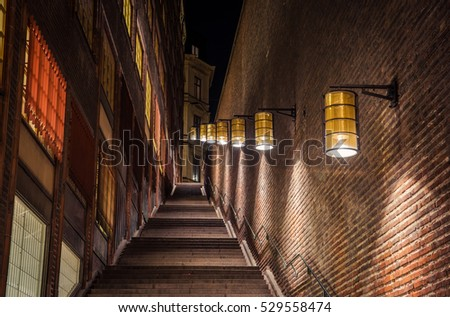 Massive stone stairs and brick walls illuminated by soft light of street lamps in central Stockholm, Sweden.