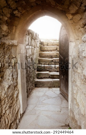 Massive stone wall with open door and rays of light behind - stock photo