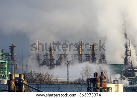 Massive white smokes coming out of factory chimney. Factory surrounded by smog. Air pollution. Industrial landscape - stock photo