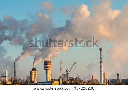 Massive white smokes coming out of many factory chimneys. Achema factory is a leading producer of nitrogen fertilizers and chemical products in Lithuania and the Baltics