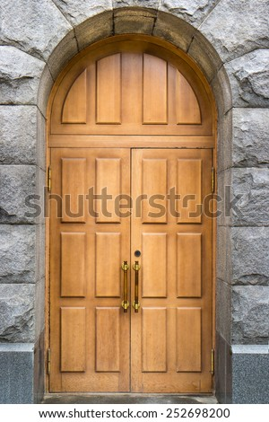 Massive wooden double door with stone arch