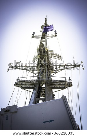 Mast and radar on battleship in blue sky background