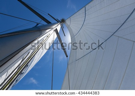 Mast and sails, close up shot from the deck looking up. Yacht sailing on a beautiful blue sunny day.