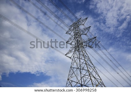 Mast electrical power line against cloud and blue sky - stock photo