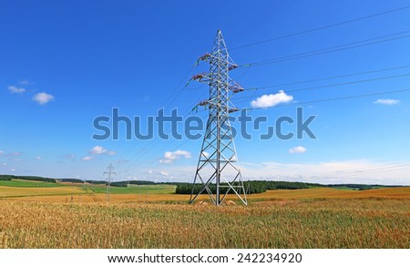 Mast electrical power line in a wheat field on a sunny day - stock photo