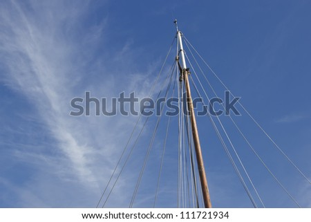 Mast of a sailboat and clouds in the sky