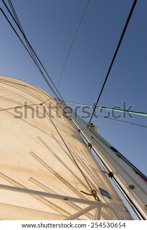 Mast, rope and sails of a yacht against an azure sky - stock photo