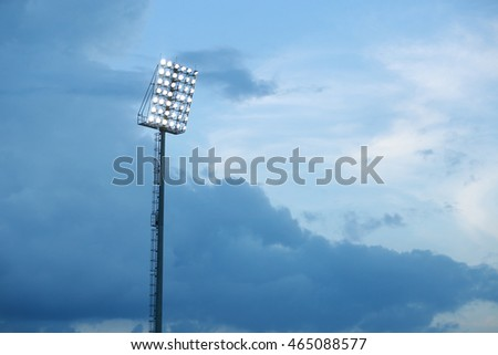 Mast with spotlights illuminate on stadium and raincloud background