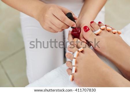 Master applying red nail polish to toenails - stock photo