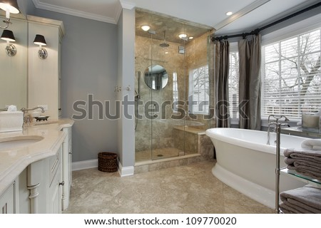 Master bat in luxury home with glass shower - stock photo
