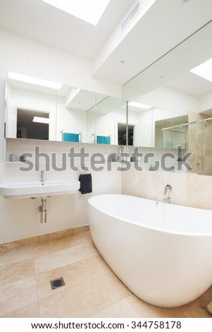 Master bathroom clean white with large bathtub in luxury Australian home - stock photo