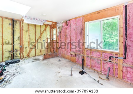 Master bathroom demolished leaving studs, insulation and plywood subflooring - stock photo