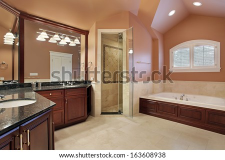 Master bathroom in luxury home with salmon colored walls - stock photo