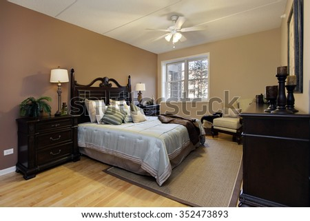 Master bedroom in condominium with dark wood furniture