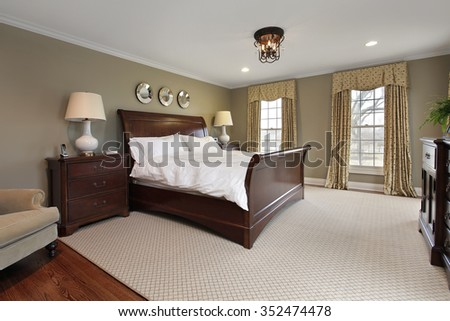 master bedroom in luxury home with dark wood bed frame