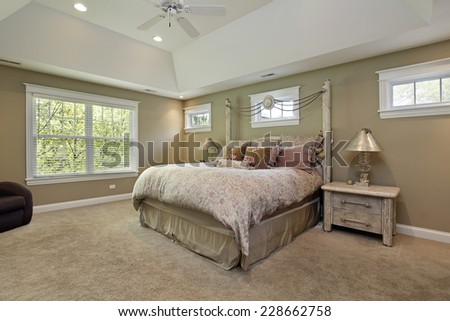 Master bedroom in luxury home with gold walls - stock photo