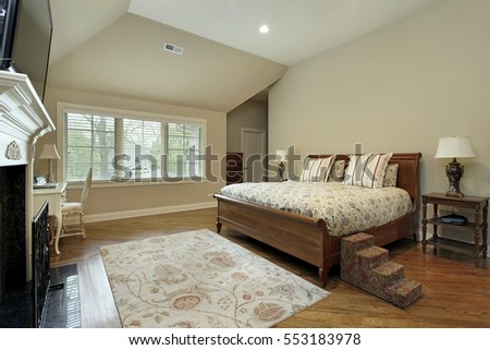 Master bedroom in upscale home with tan walls.