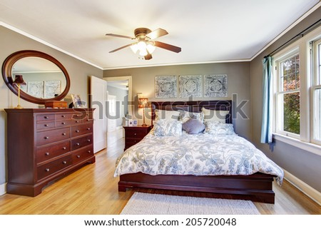 Master bedroom interior in light grey color. View of queen size bed and dresser - stock photo