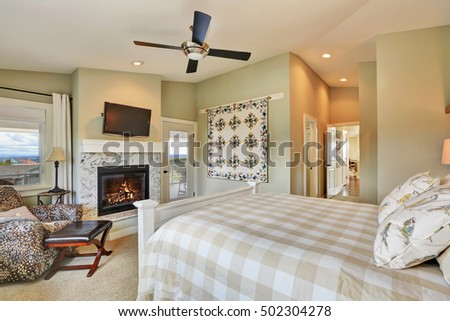 Master bedroom interior with fireplace and light olive walls. Northwest, USA