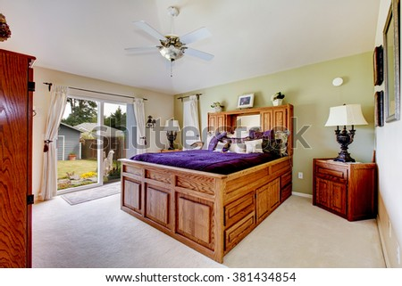 Master bedroom with elegant purple bedding and white carpet.