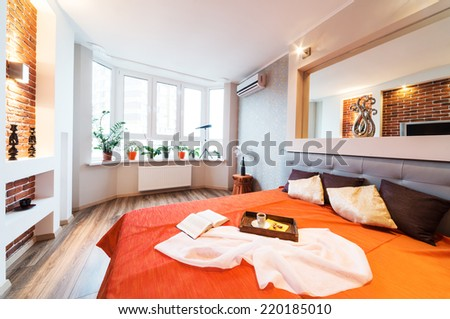 Master bedroom with king size bed, large mirror and open curtains - stock photo