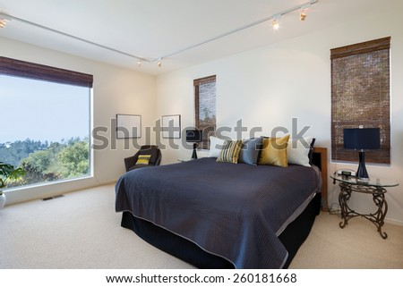 Master bedroom with view window, armchair, pillows and Matchstick wood Roll Up Blinds in luxury home. - stock photo