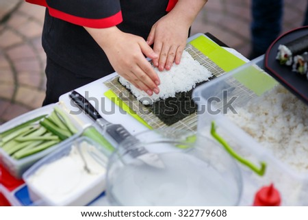 Master chef preparing delicious wedding sushi outdoors with a variety of ingredients - stock photo