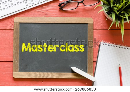 Master class handwritten on blackboard. Master class Handwritten with chalk on blackboard, keyboard,notebook,glasses and green plant on wooden background - stock photo
