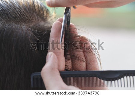 master hairdresser and stylist in the workflow closeup - stock photo
