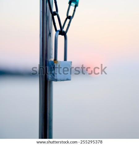 Master key locked on grunge iron gate - stock photo