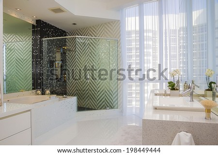 Master luxury bathroom in contemporary green zigzag decor and heavy granite counter tops  - stock photo